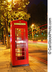 English telephone booth in the night with long exposure traffic lights in the background