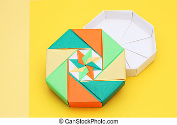 origami paper box - colorful origami paper box on a yellow...