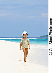 A young girl walking on the beach