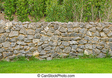 fence real stone wall surface with cement on green grass...