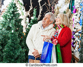 Couple Shopping At Christmas Store - Senior couple with bags...