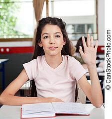Schoolgirl Raising Hand In Classroom - Little schoolgirl...