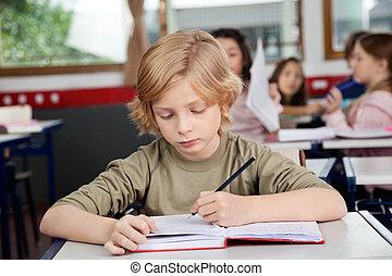 Schoolboy Writing In Book At Desk - Cute schoolboy writing...