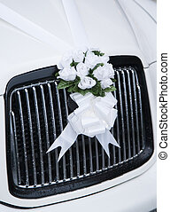 White wedding flowers on a car grill