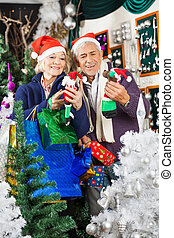 Couple Shopping For Christmas Decorations - Senior couple in...