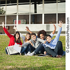 College Students With Hands Raised Sitting At Campus -...