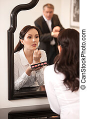 Please, hurry up Confident middle-aged woman doing make-up...