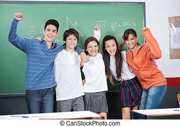 Joyful Schoolchildren Standing Together In Classroom -...