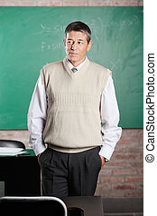 Teacher With Hands In Pockets Looking Away In Classroom -...