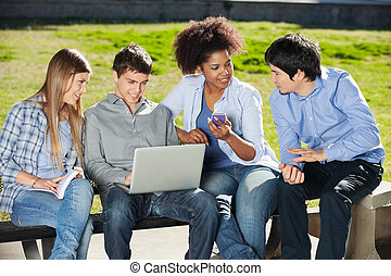 Students With Laptop And Mobile phone Sitting In Campus -...