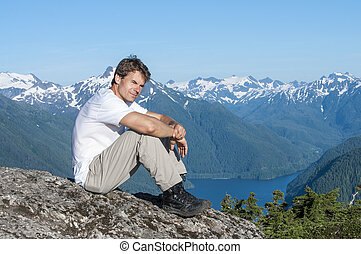 On top of the world - Caucasian man sits on rock on mountain...