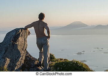 Joy of hiking - Shirtless Caucasian male hiker stands on top...