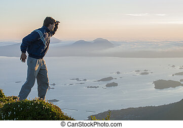 Look out - Caucasian male hiker on top of mountain looks out...