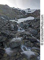 Snow melt - Clear mountain stream forms from summer snow...