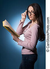 Woman with book. Confident young woman in glasses holding a...