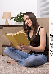 Reading at home. Beautiful young woman sitting on the floor at home and reading book