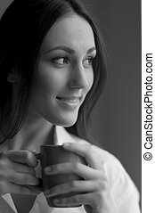 Woman with cup of coffee. Black and white image of beautiful...