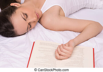 Woman sleeping. Beautiful young woman sleeping with open book lying near her