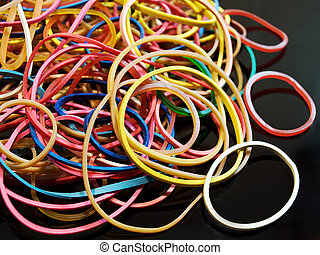 Rubber - Bunch of colorful and elastic rubber on a black...