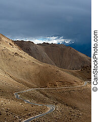 Empty rural road going through Himalaya high mountain landscape panorama with dramatic cloudy sky. India, Ladakh