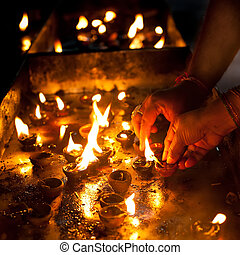 People burning oil lamps as religious ritual in Hindu temple. India