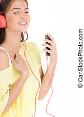 Relaxing with her favourite music. Beautiful young woman in headphones listening to the music and keeping her eyes closed while standing isolated on white