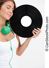 Music lover. Beautiful young woman holding vinyl record in her hand and keeping her eyes closed while standing isolated on white