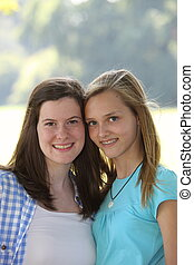 Two attractive smiling young teenage girls