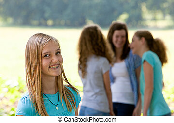 Attractive teenage girl with dental braces standing smiling...
