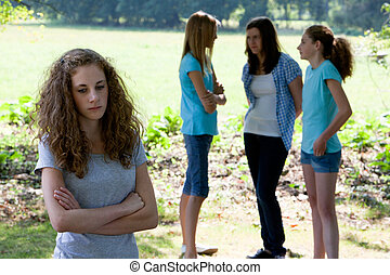 Outcast - Sad young teenage girl standing with folded arms...