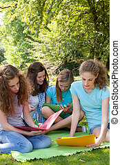 Young female college friends studying outdoors - Group of...