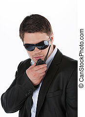 Bodyguard Confident young man in sunglasses talking on radio...