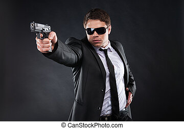 Bodyguard. Confident young man in formalwear holding gun and...