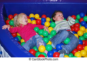 boy to a girl playing in the pool with colorful balls.