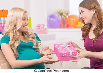 Baby shower. Beautiful pregnant woman receiving gift from...