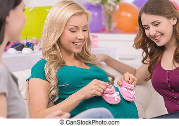 Young women on baby shower Beautiful pregnant woman showing...
