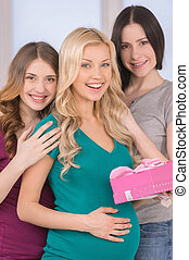 Happy friends on Baby Shower. Beautiful pregnant woman...