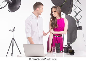 Photographer and model. Young man talking to fashion model at studio