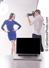Photographer and model. Young photographer shooting model at studio