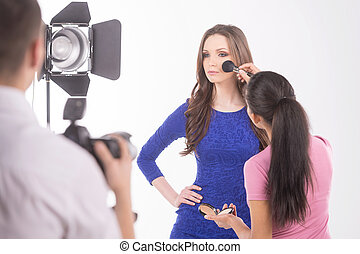 Photographer and model. Rear view of photographer shooting fashion model at studio