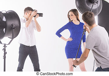 Photographer and model. Photographer shooting fashion model at studio while young man assisting with the light
