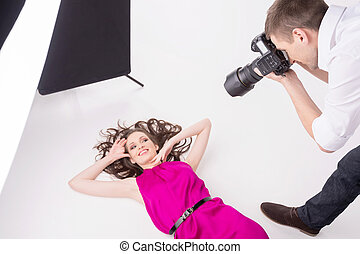 Photographer and model. Top view of young man photographing model at studio