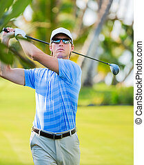 Athletic young man playing golf, golfer hitting fairway...