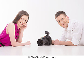 Photographer and model. Young man with camera and fashion model lying face to face and looking at camera