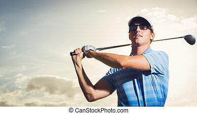 Golfer at sunset, Man swinging golf club with dramatic...