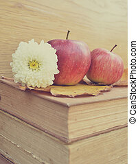 Apple on old books and flowers