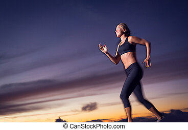 Athletic woman running at sunset dusk with motion blur -...