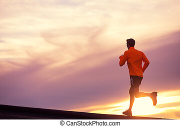 Male runner silhouette, running into sunset