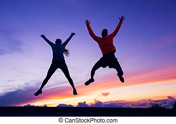 Happy man and woman having fun jumping into air at sunset