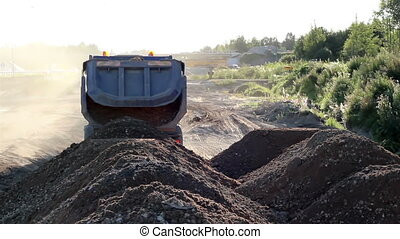 Pile of soil is being dumped by a Dumptruck roadworks - A...